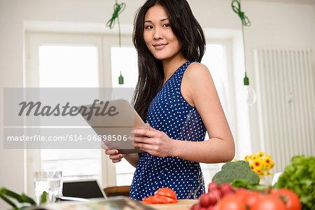 Woman holding digital tablet looking at camera
