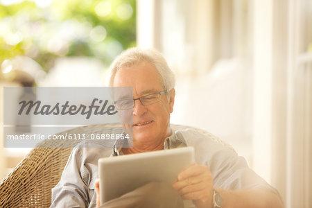 Senior man using digital tablet on patio