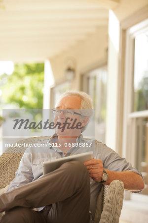 Smiling senior man using digital tablet on porch