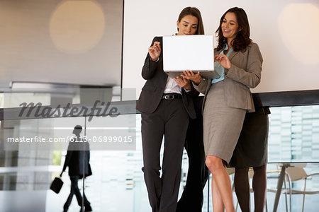 Businesswomen using laptop in lobby