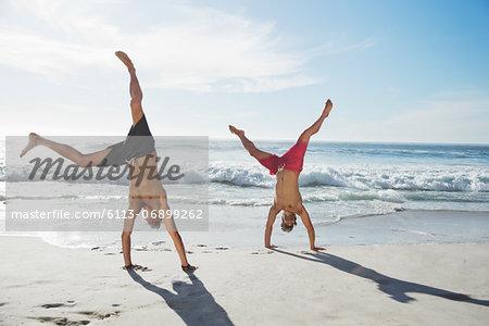Men in swim trunks doing handstands on beach