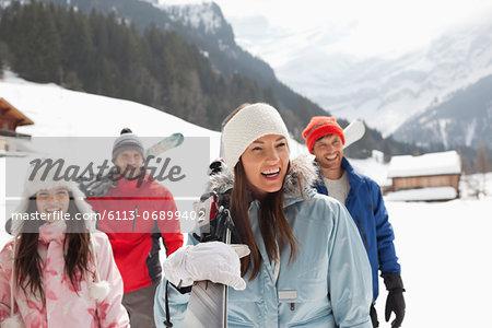 Happy friends carrying skis in snowy field