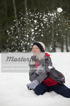 Portrait of happy boy enjoying snowball fight
