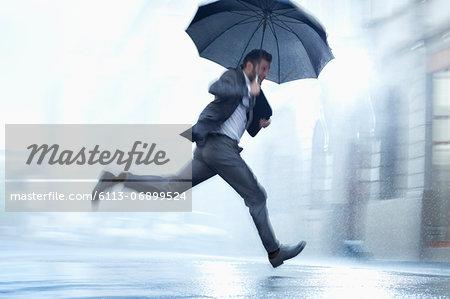 Businessman running with umbrella in rainy street