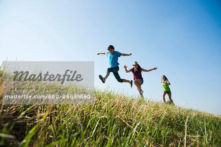 Girls running up hill, Germany