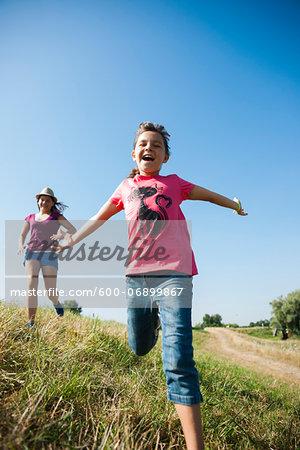 Girls running in field, Germany