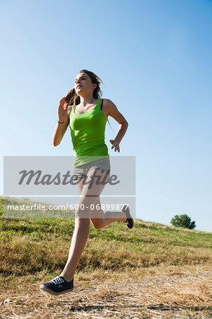 Teenaged girl running in field, Germany