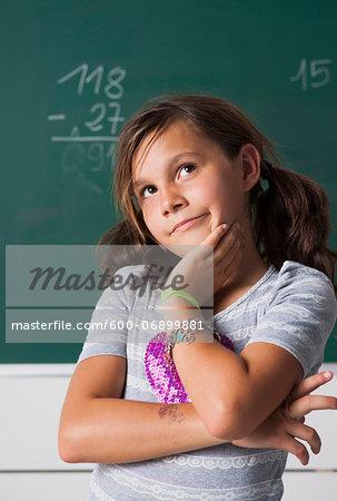 Portrait of girl standing in front of blackboard in classroom, Germany