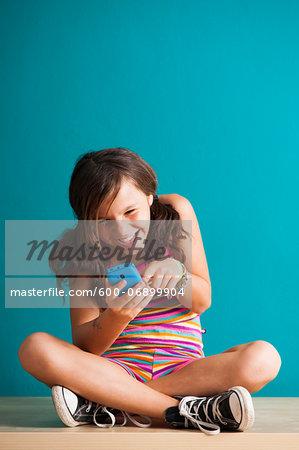 Girl sitting on floor looking at smartphone, Germany