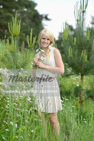 Portrait of blond woman holding oxeye daisy flowers in meadow, Germany