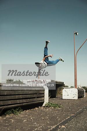 Teenaged boy doing handstand on barrier, freerunning, Germany