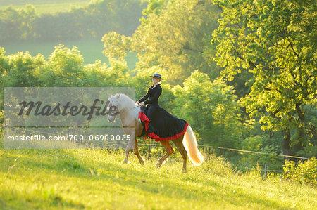 Woman Wearing Dress Riding a Connemara Stallion on a Meadow, Germany