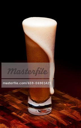 Glass Mug of Beer with Foam Spilling Over