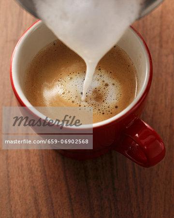 Milk foam being poured onto espresso