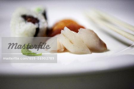 Uramaki and nigiri sushi; sashimi and wasabi paste to the front