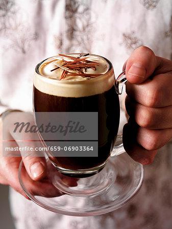 Hands holding a glass mug of Irish coffee