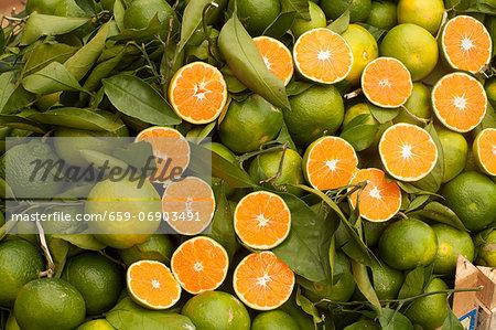 Many Fresh Organic Sicilian Oranges; Some Whole, Some Halved; Leaves
