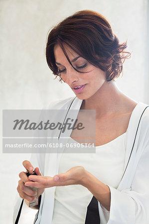 Woman spraying perfume onto her fingers