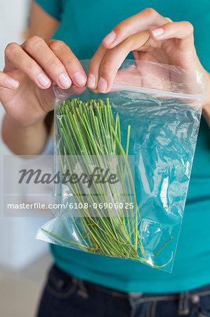 Woman packing leaf vegetables for storage