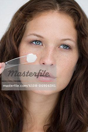 Woman applying moisturizer cream on her face