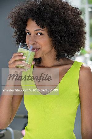 Portrait of a woman drinking kiwi shake
