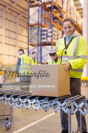 Worker scanning box on conveyor belt in warehouse