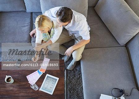 Couple using tablet computer on sofa