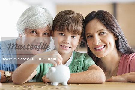 Three generations of women filling piggy bank