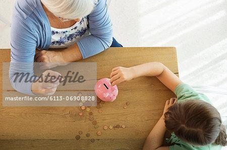 Older woman and granddaughter filling piggy bank