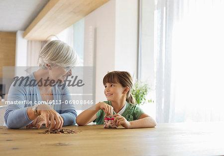 Older woman and granddaughter filling change jar