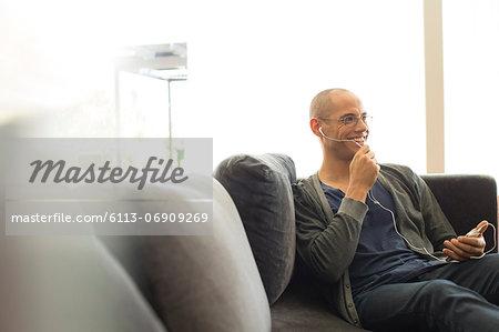 Man talking on headset on sofa