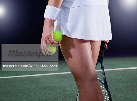 Tennis player holding balls on court