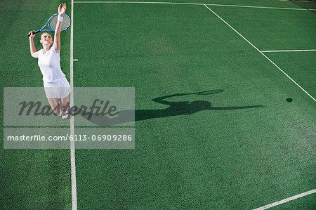 Tennis player serving ball on court