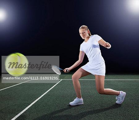 Tennis player hitting ball on court