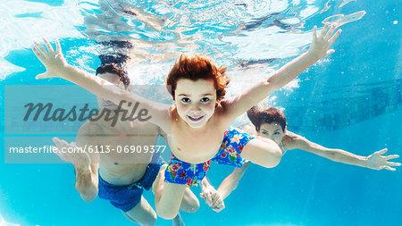Family swimming in pool