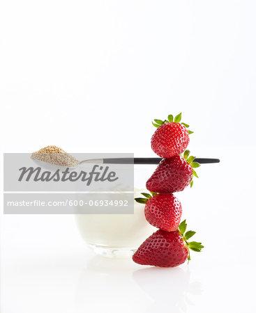 Stack of Fresh Strawberries, Glass of Greek Yogurt and Spoon of Ground Flax Seeds, Studio Shot