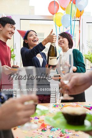 Woman Opening Champagne Bottle in Office