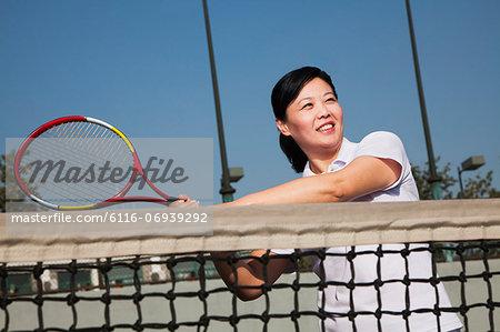 Mature woman playing tennis, portrait