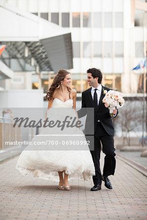 Bride and Groom walking towards camera along walkway in City Park on Wedding Day, Toronto, Ontario, Canada