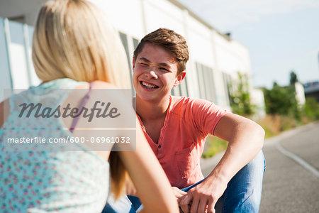 Teenage girl and teenage boy sitting on street, talking, Germany
