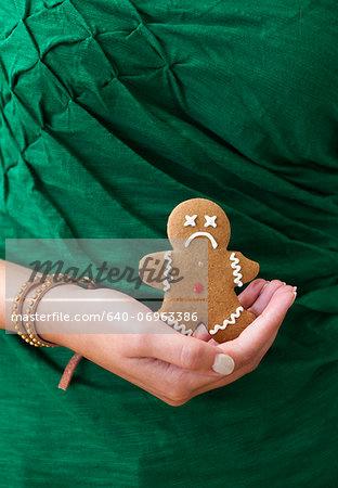 Woman's hand holding sad gingerbread man