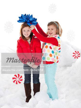Studio portrait of girls (4-5, 6-7) standing in snow