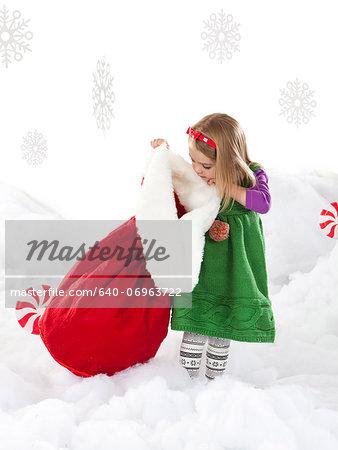 Studio shot of girl (18-23 months) peeking to Santa bag