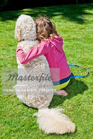Teen girl with arm around white dog