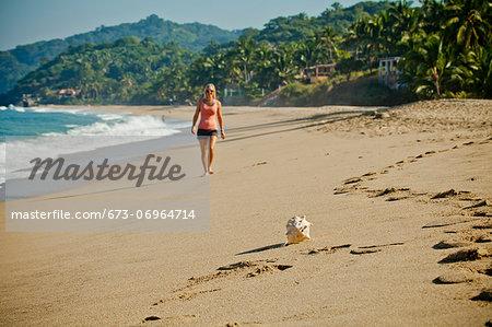Woman walking on beach toward seashell