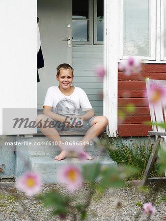 Teenage boy sitting on porch