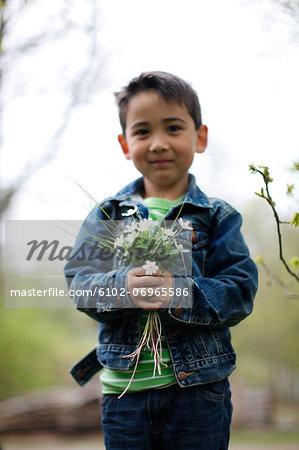 Smiling boy holding flowers
