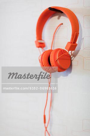 Orange headphones hanging on wall