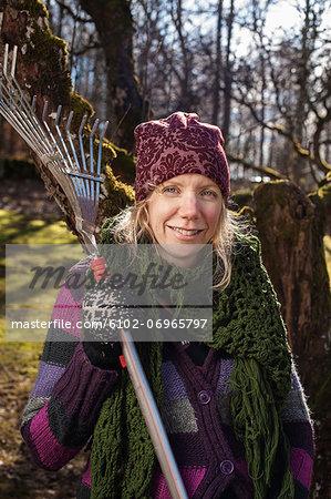 Smiling woman holding rake