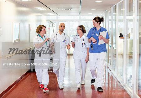 Team of doctors communicating while walking in hospital corridor